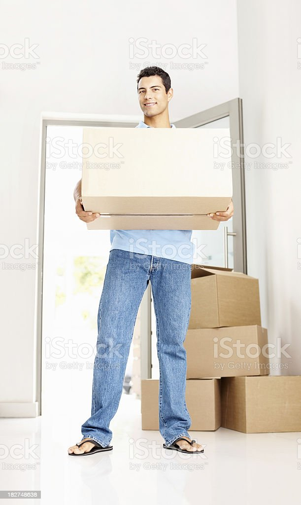 Young man with box moving into new home royalty-free stock photo