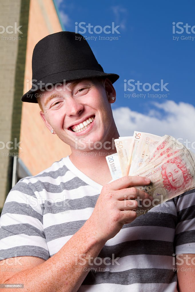 Young Man with British Pounds and Euros royalty-free stock photo