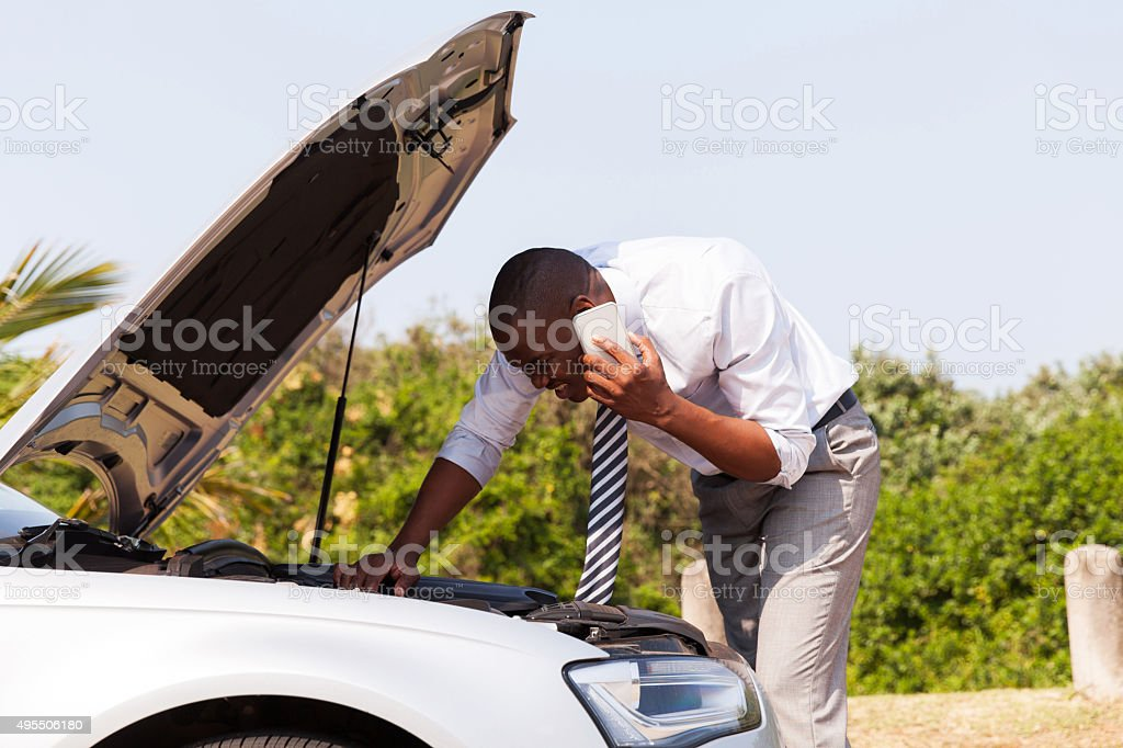 young man with broken down car calling for help stock photo
