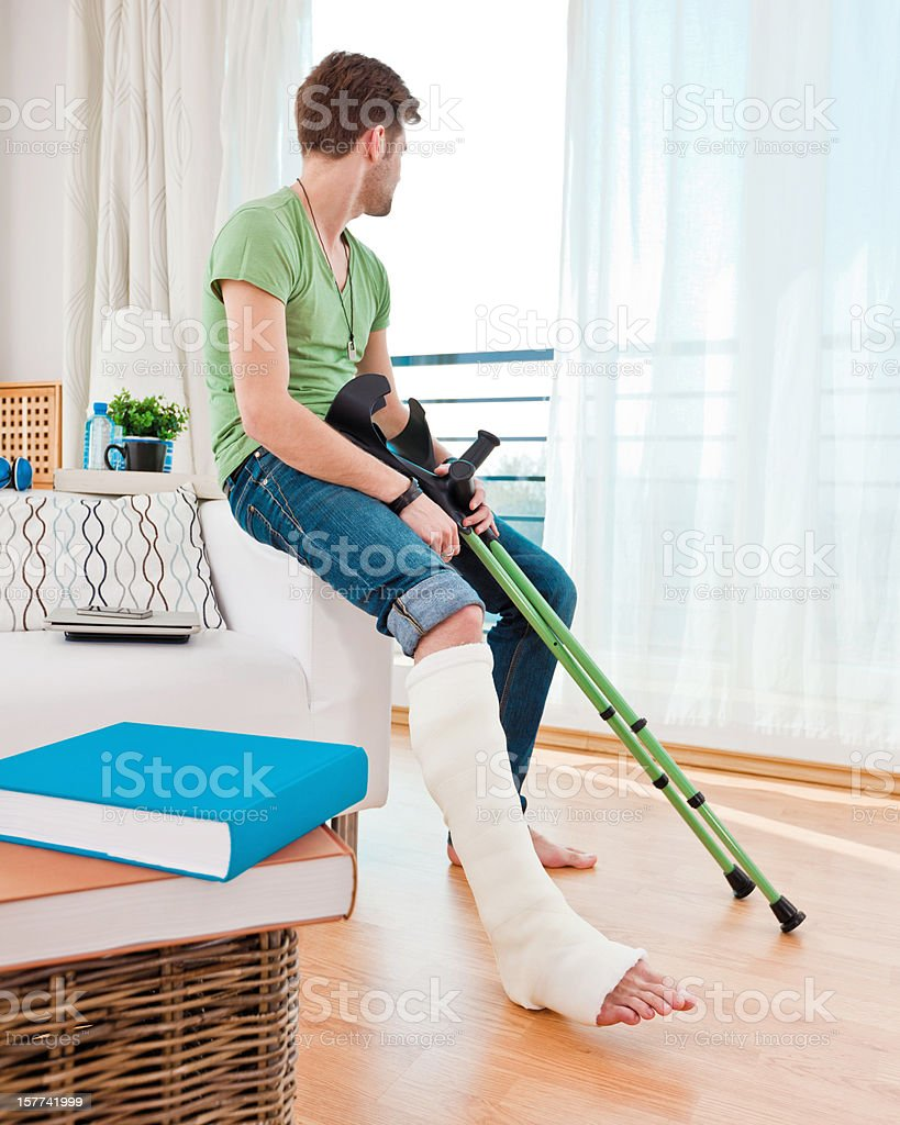 Young man with broken leg at home royalty-free stock photo