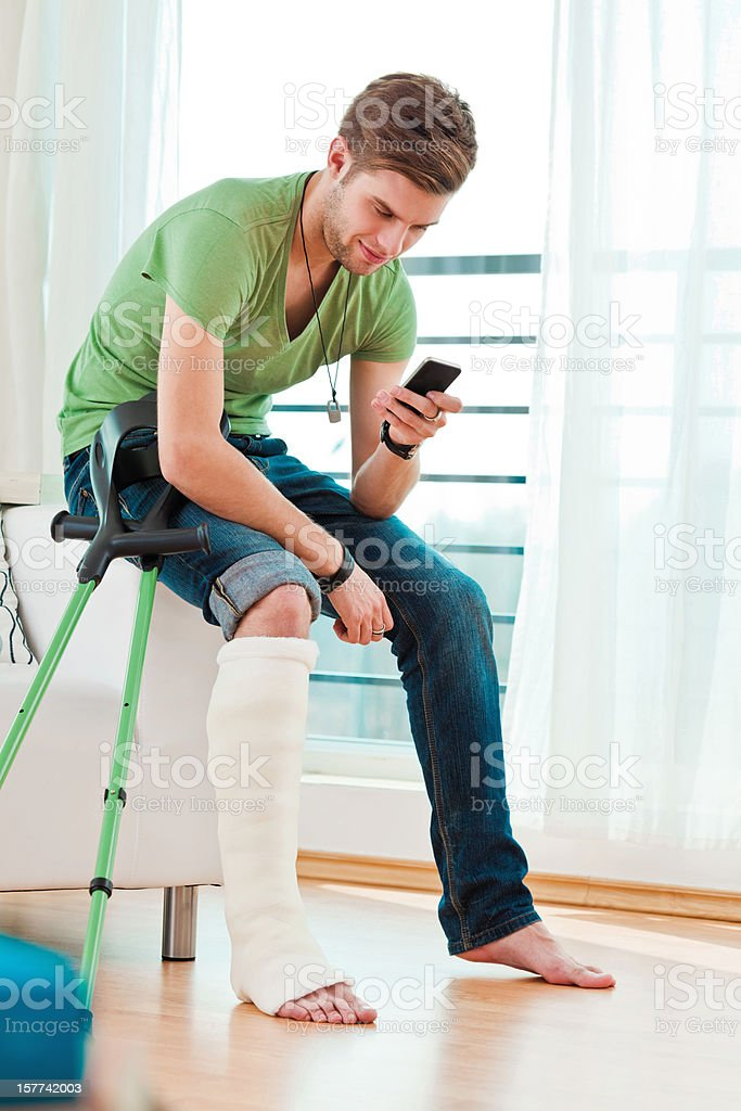 Young man with broken leg at home stock photo