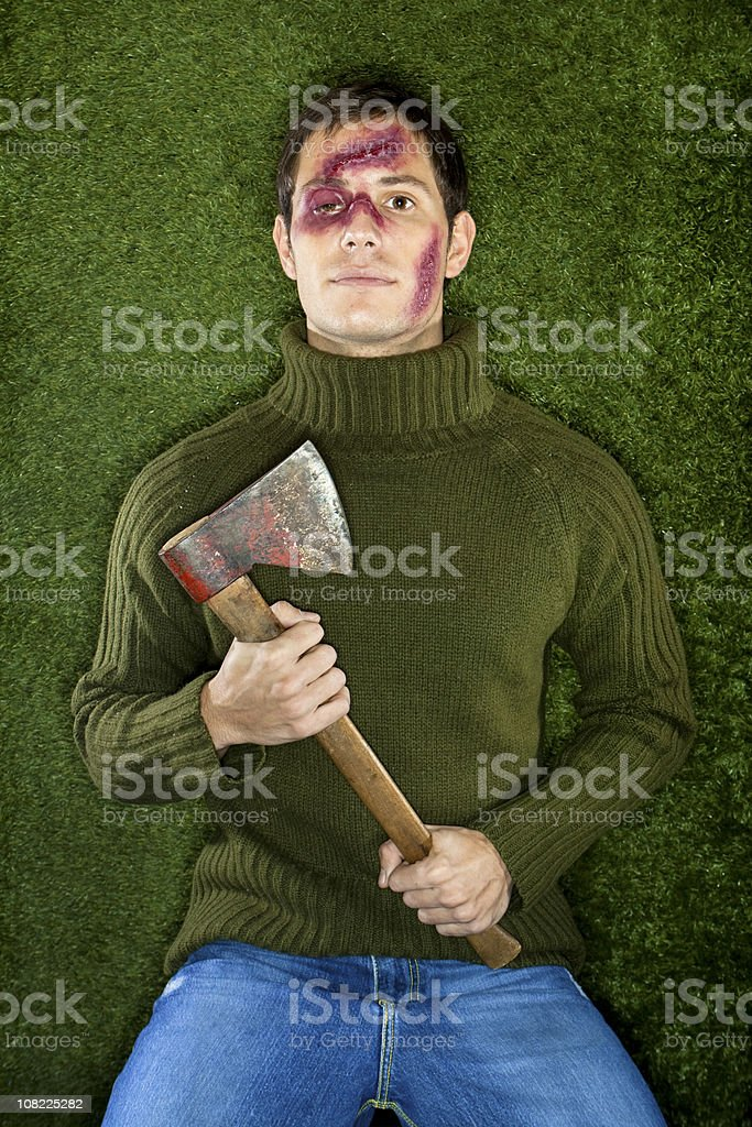 Young Man with Bruised and Cut Face Holding Axe stock photo