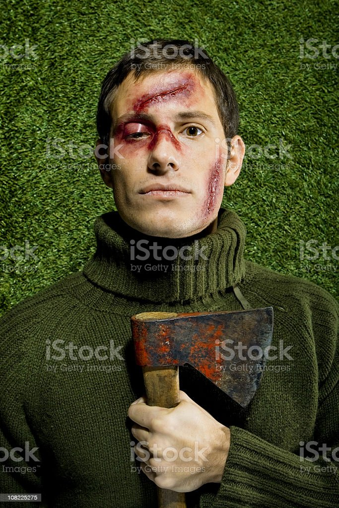 Young Man with Bruises and Cuts on Face Holding Axe stock photo