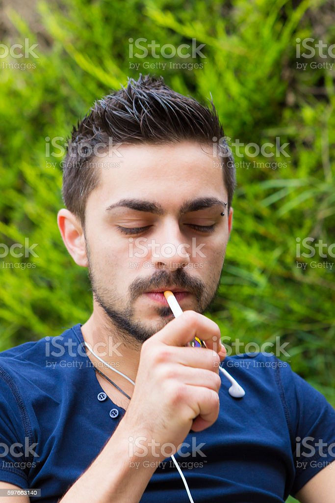 Young man with cigarette outdoors stock photo