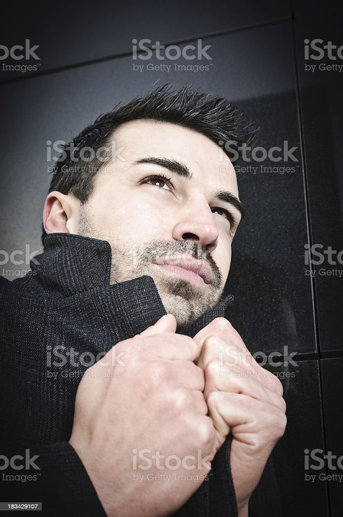 Young Man with Coat feeling Cold looking up royalty-free stock photo