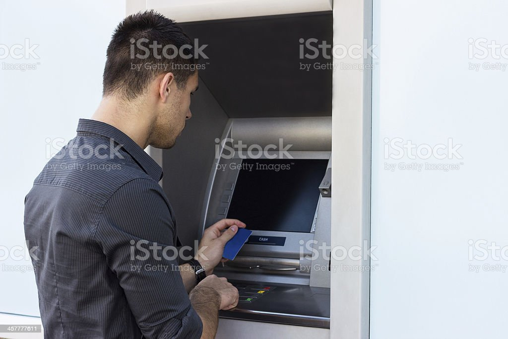 Young man with credit card at the ATM royalty-free stock photo