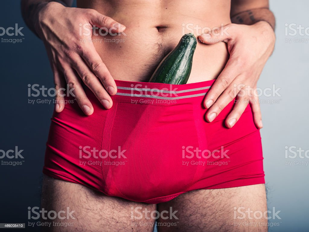 Young man with cucumber in his underpants stock photo