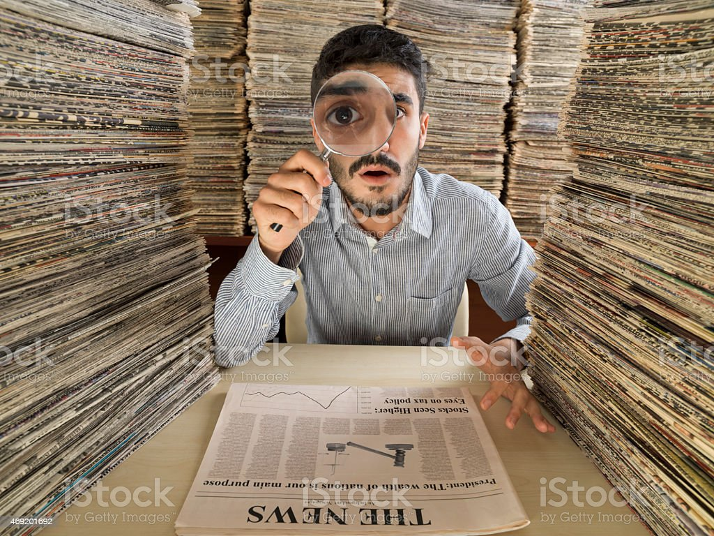 Young man with dark hair doing research in newspaper archive stock photo
