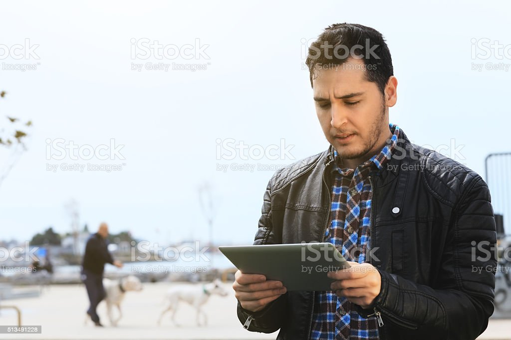 Young man with digital tablet at the park stock photo