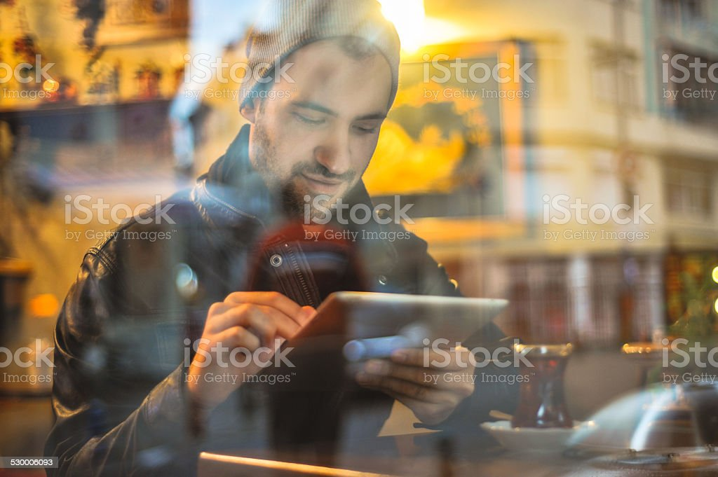 Young man with digital tablet sitting in a cafe stock photo