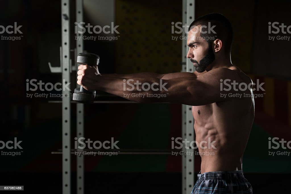 Young Man With Dumbbells Exercising Shoulders stock photo