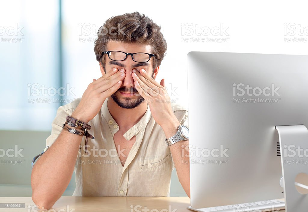 Young man with eyes pain touching his eyes stock photo