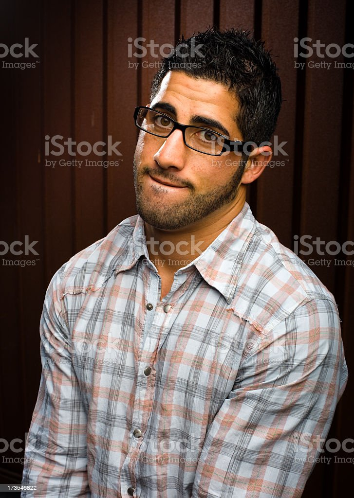 young man with glasses biting lip royalty-free stock photo