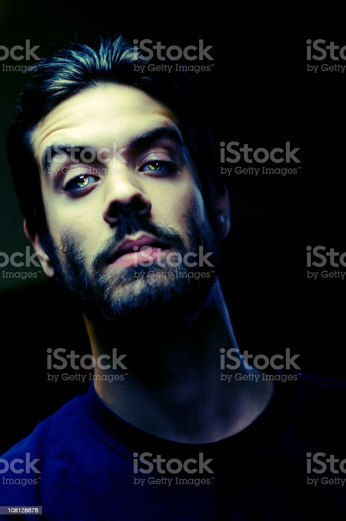 Young Man With Glowing Eyes on Black Background royalty-free stock photo