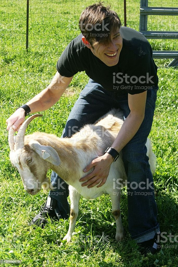 young man with goat royalty-free stock photo