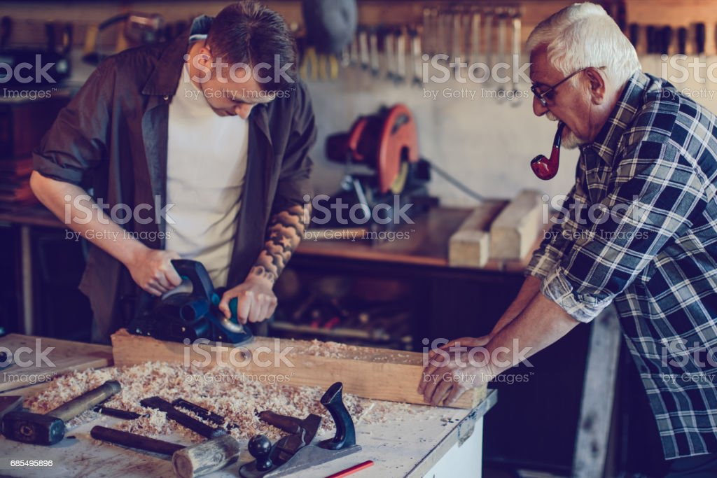 Young man with grandpa at workshop stock photo