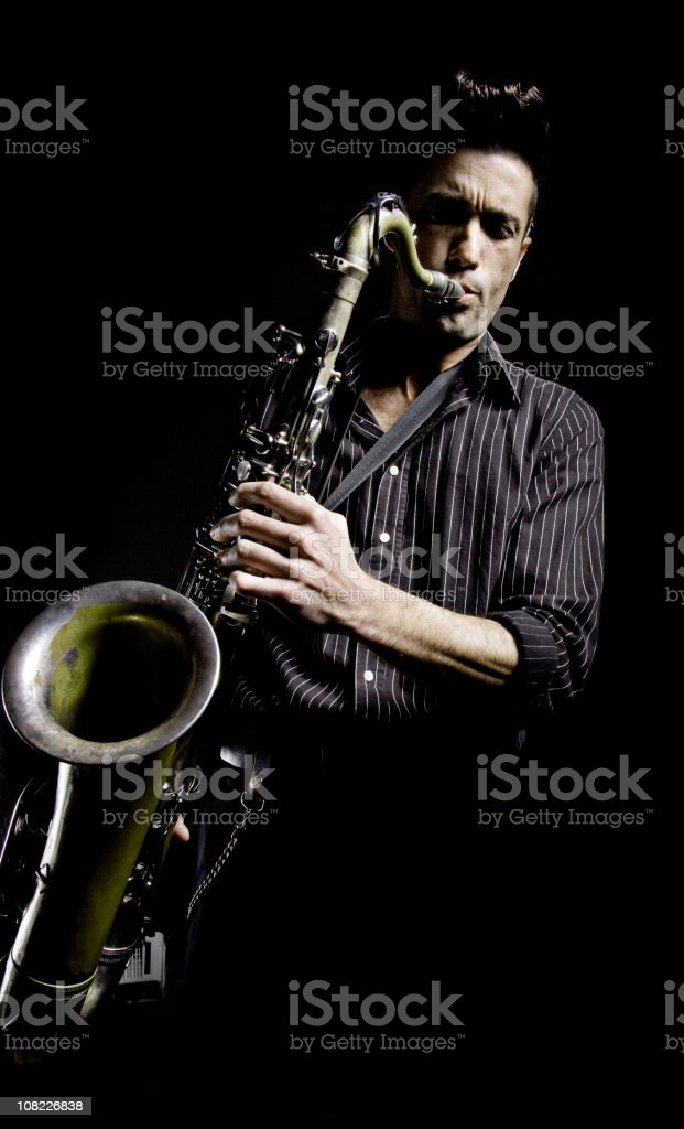 Young Man with Greased Hair Playing Saxophone, Low Key royalty-free stock photo