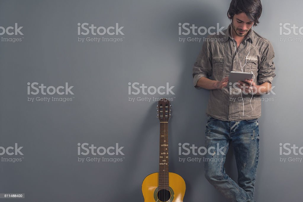 young man with guitar and tablet stock photo