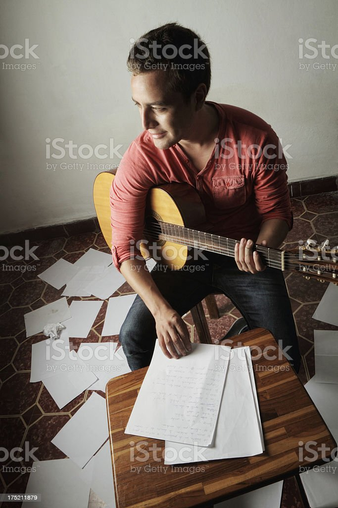 Young man with guitar composing song stock photo