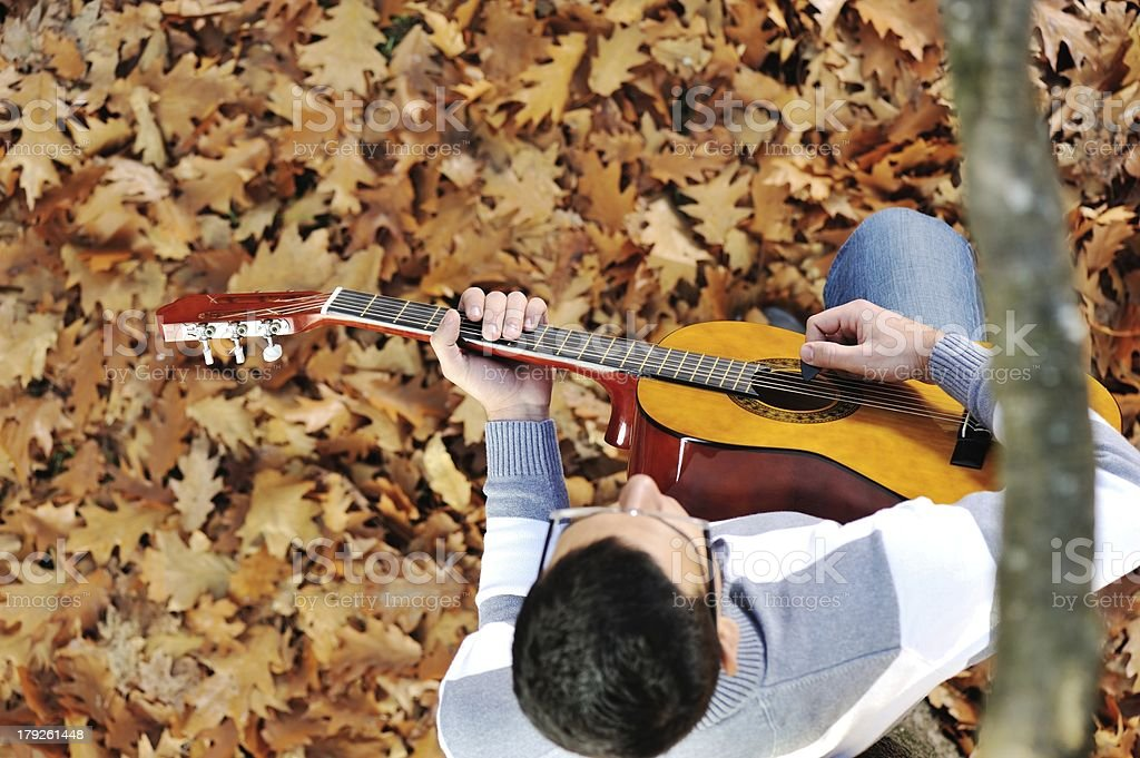 Young man with guitar in park royalty-free stock photo