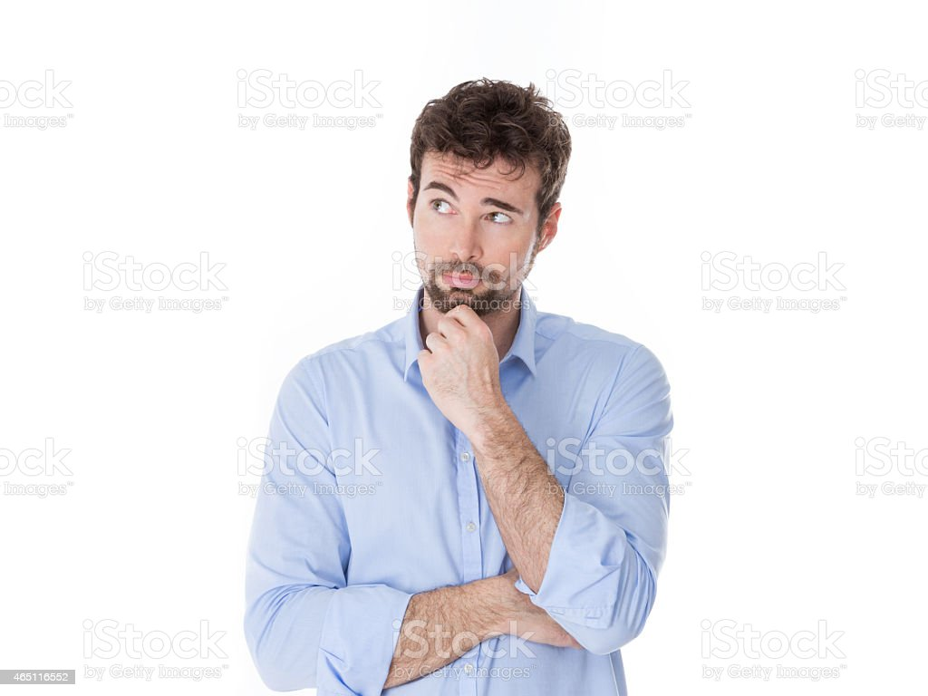 young man with hand on chin thinking stock photo