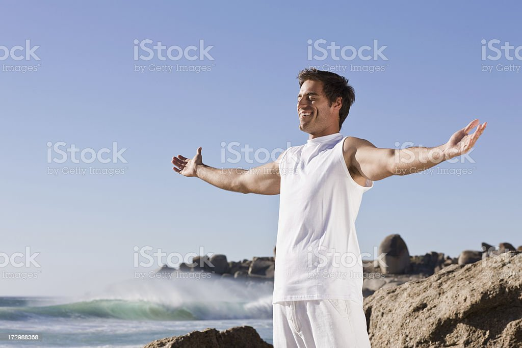 Young man with hands outstretched standing by sea royalty-free stock photo