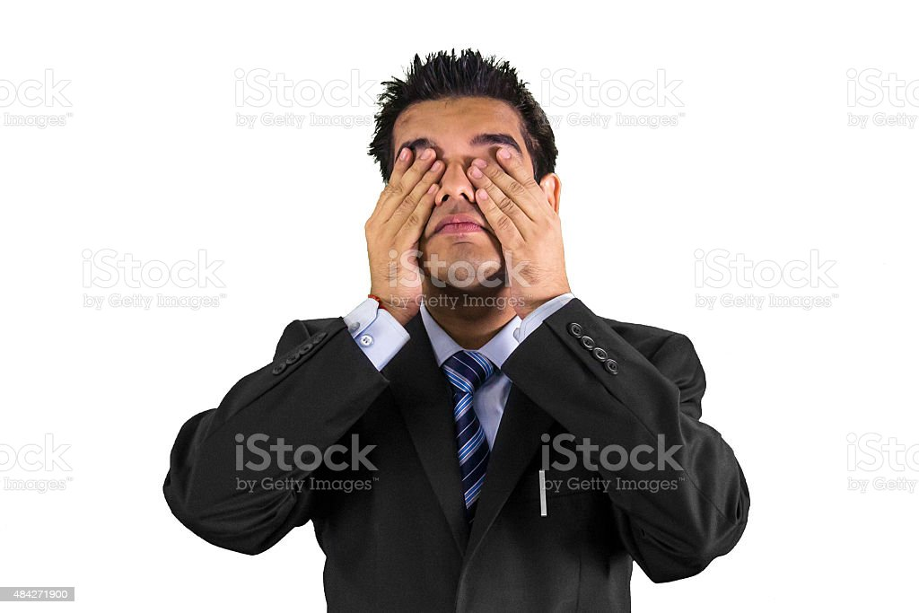 Young man with hands over his eyes stock photo