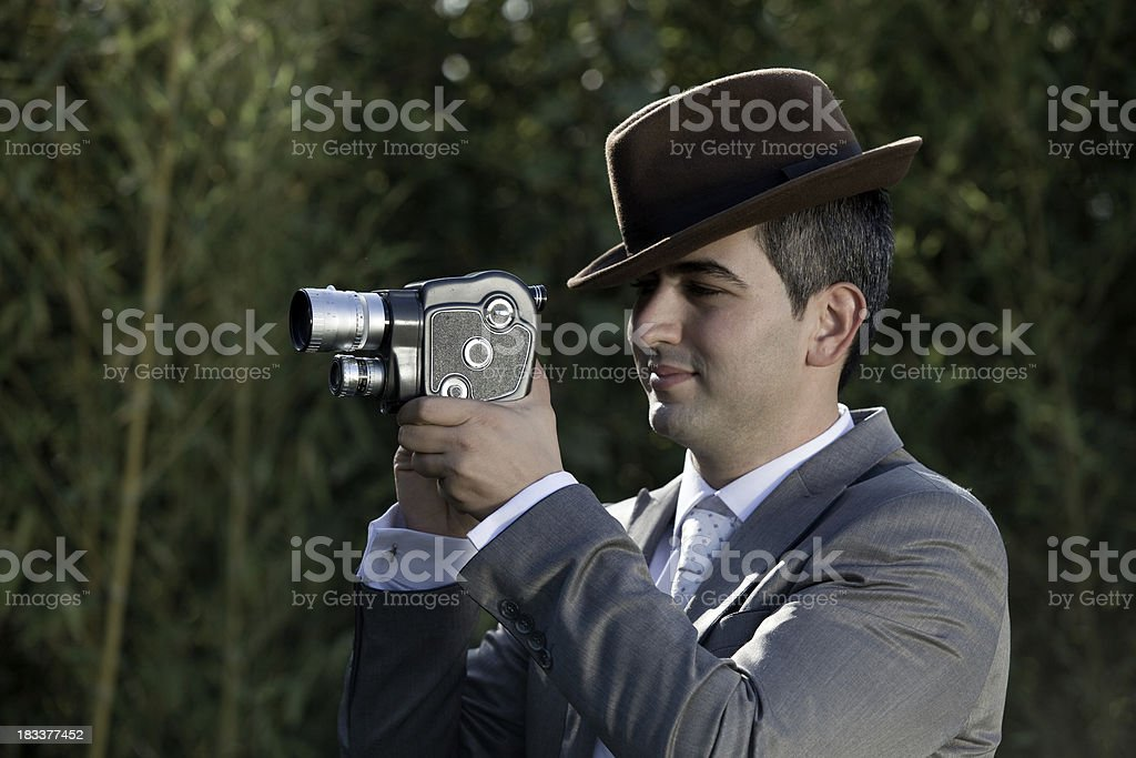 Young man with hat filming via old fashioned 8mm camera royalty-free stock photo