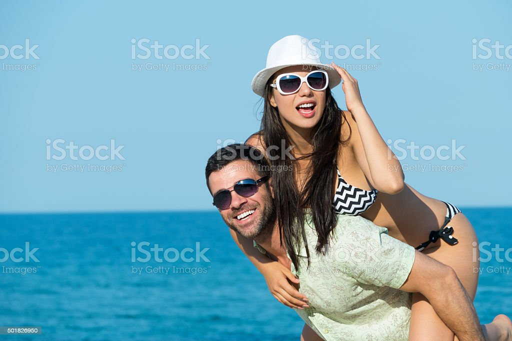 Young man with hat piggybacking his girlfriend on the beach stock photo