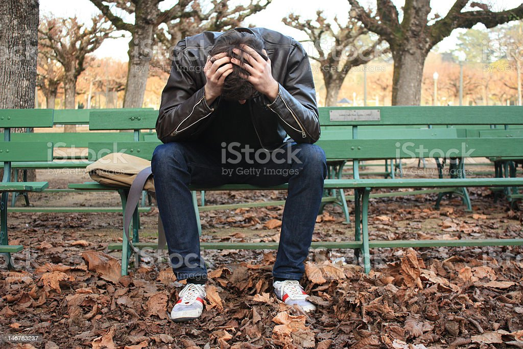 young man with head in hands stock photo