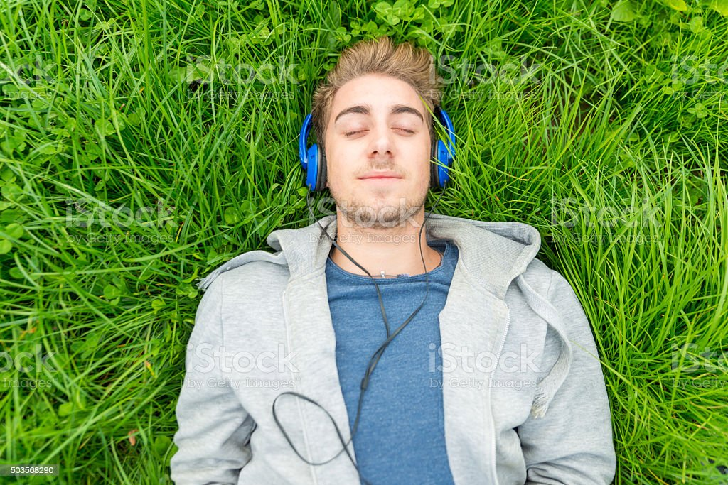 Young man with headphone listening to music in park stock photo