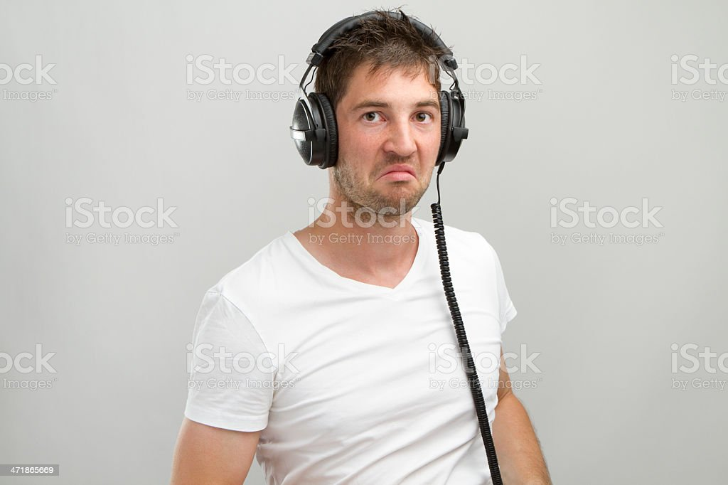Young Man with Headphones dislikes what he hears. royalty-free stock photo