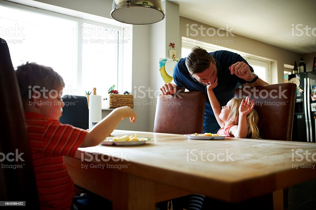 Young man with his children at dining table stock photo