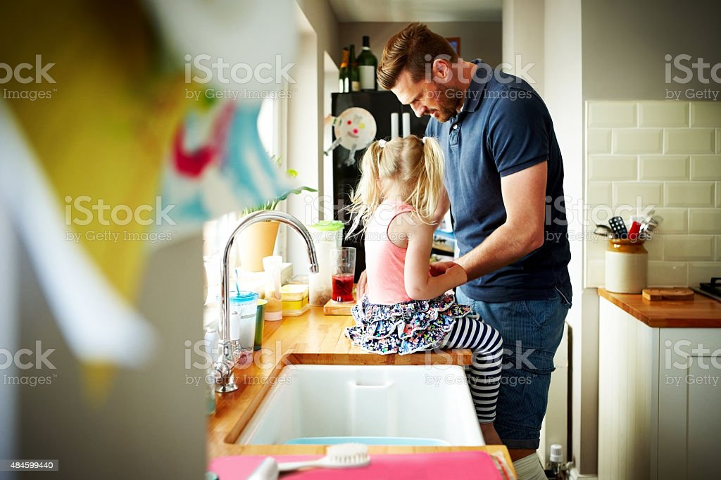 Young man with his daughter preparing lunch in kitchen stock photo