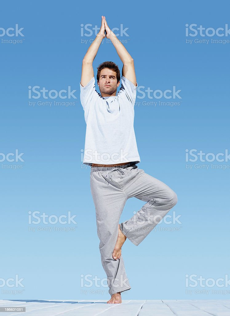 Young man with his hands joined practicing yoga royalty-free stock photo