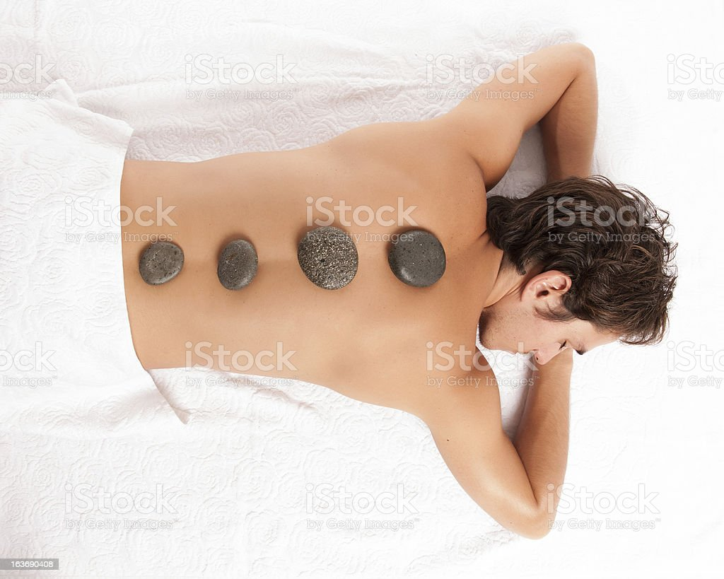 young man with hot stone massage. stock photo