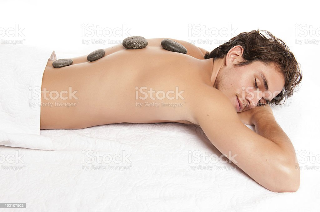 young man with hot stones on his back. stock photo