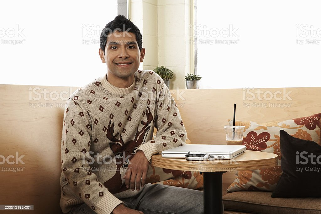 Young man with iced coffee, laptop and cell phone in cafe, portrait stock photo