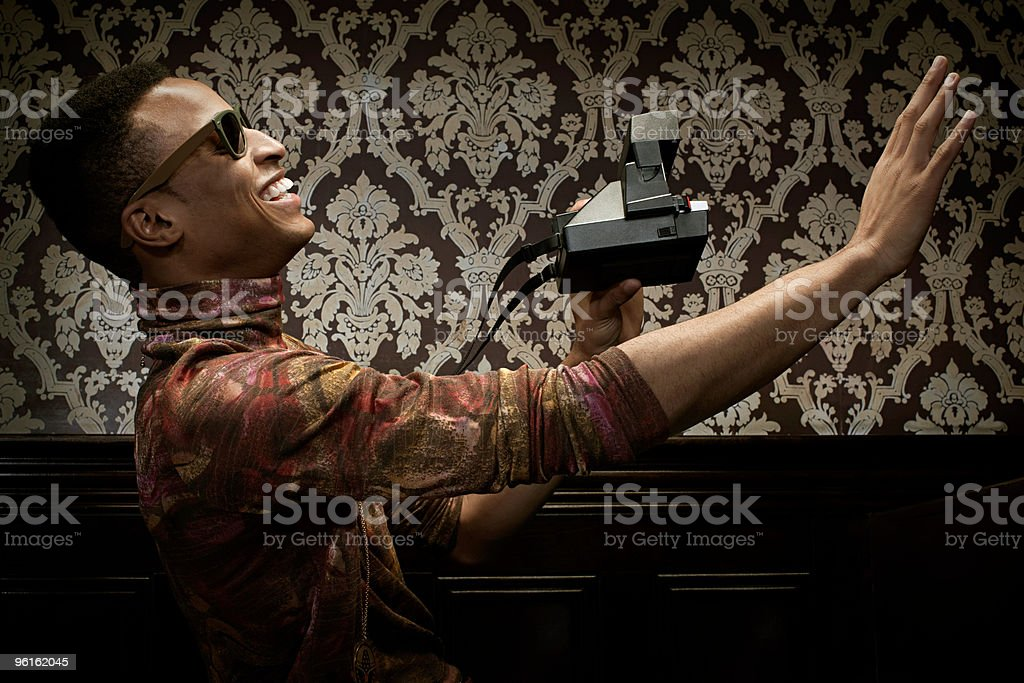 Young man with instant camera stock photo