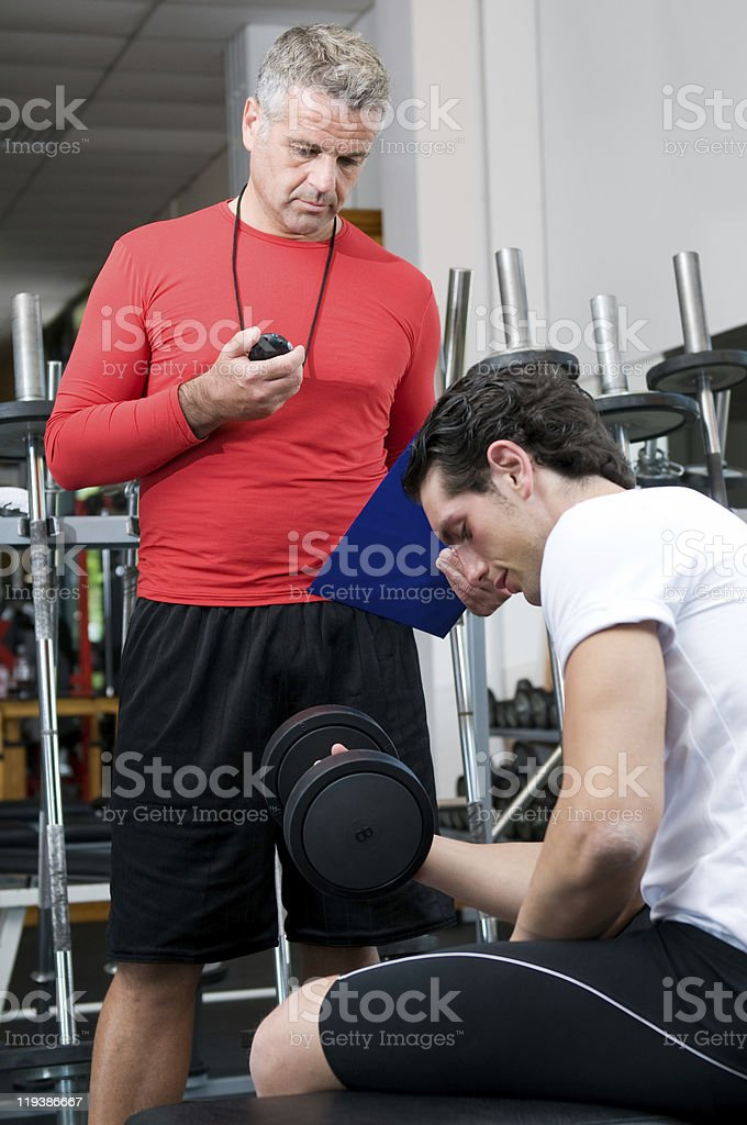 Young man with instructor at gym stock photo