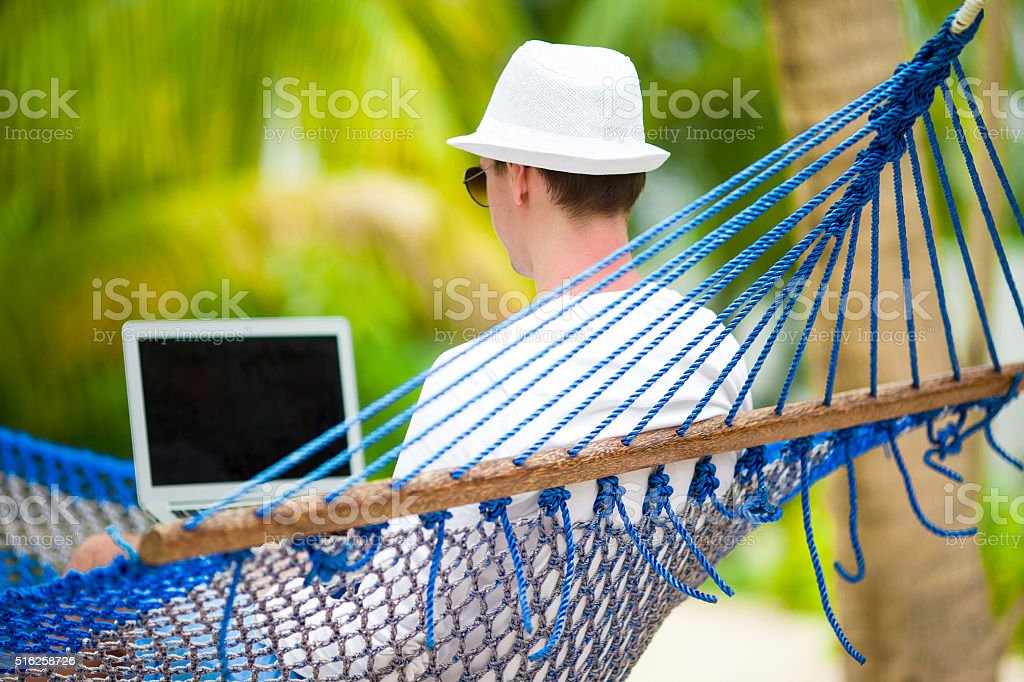 Young man with laptop at hammock on tropical vacation stock photo