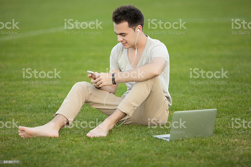 young man with laptop outdoor stock photo
