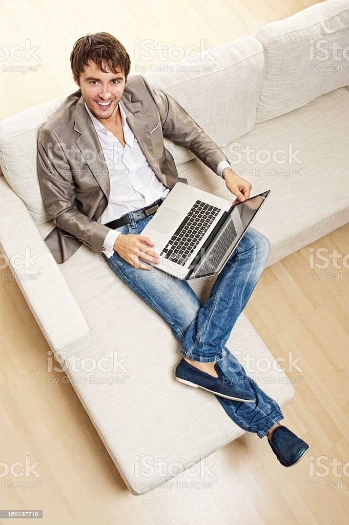 Young man with  laptop sitting on a sofa royalty-free stock photo