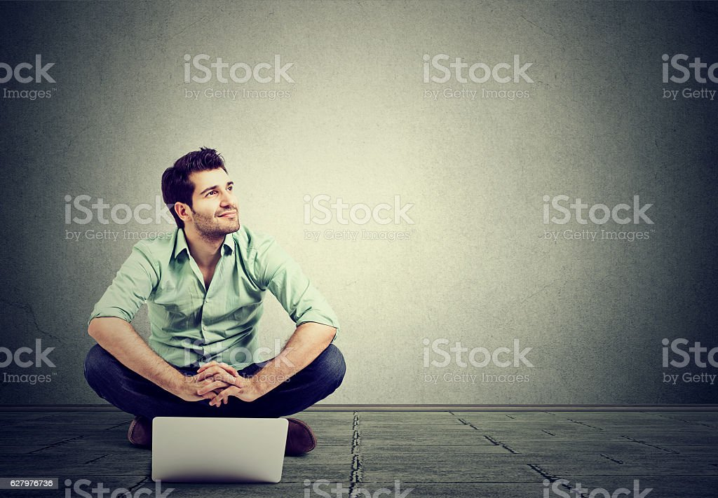young man with laptop sitting on floor stock photo