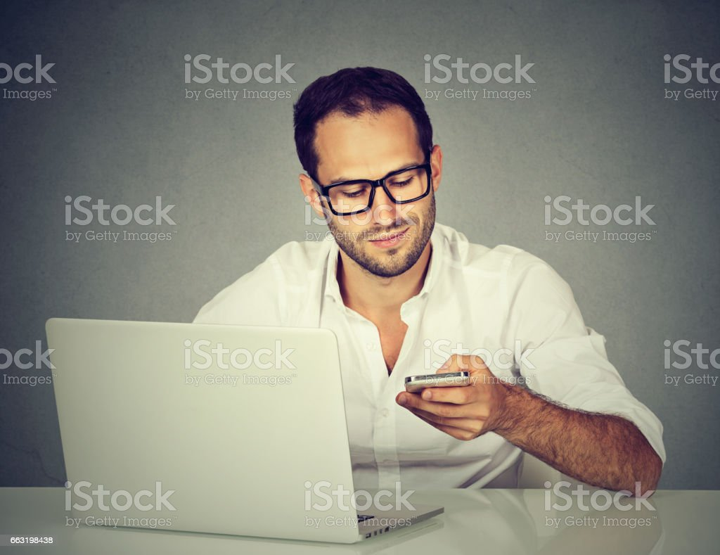 Young man with laptop texting on mobile phone sitting at table stock photo
