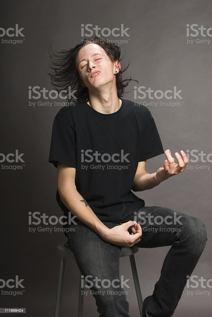 Young man with long flying hair  playing air guitar royalty-free stock photo