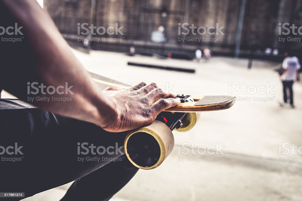 Young man with longboard taking a break stock photo