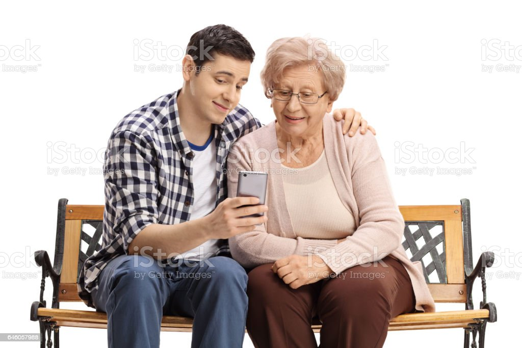 Young man with mature woman showing her something on phone stock photo