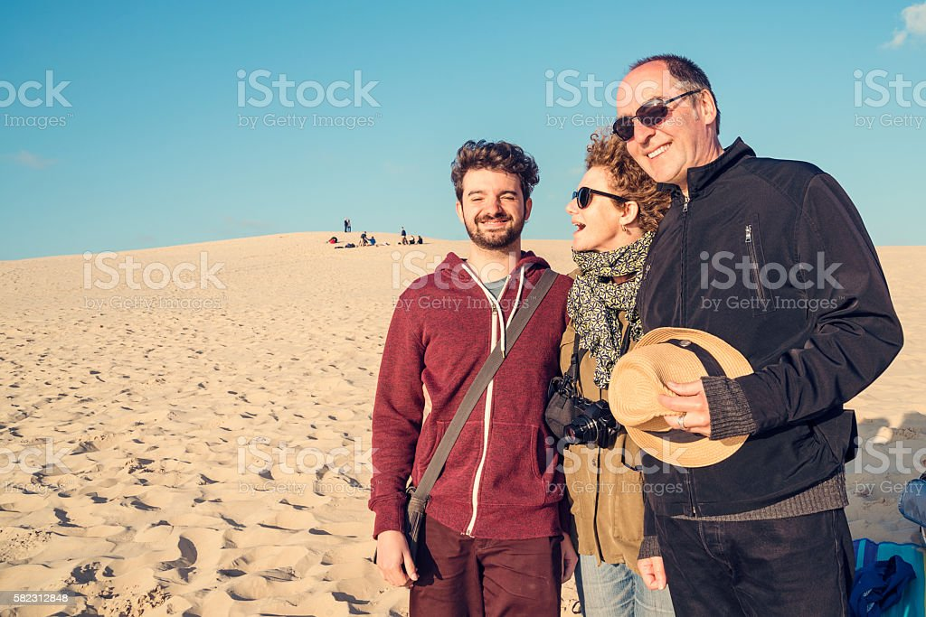 Young man with middle-age parents on sand dune. stock photo