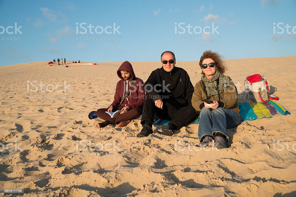 Young man with middle-age parents sitting on sand dune. stock photo